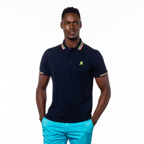 Model wearing navy blue polo with green, red, blue, and peach striped collar, matching ribbed armbands, and embroidered green frog mascot.