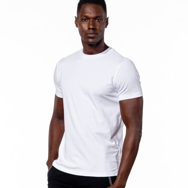"Model in white, short-sleeve cotton crew-neck with embroidered ""EX"" logo on left sleeve."