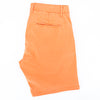 Folded orange shorts with back welt pocket.