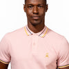 Model in light-pink polo with tipped collar, two-button placket, and striped, ribbed armbands. Featuring embroidered gold frog mascot.
