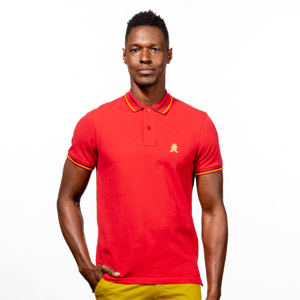 Model in red polo with tipped collar, two-button placket, and striped, ribbed armbands. Featuring embroidered gold frog mascot.