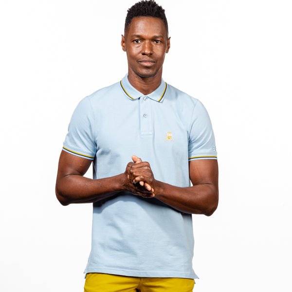 Model in light-blue polo with tipped collar, two-button placket, and striped, ribbed armbands. Featuring embroidered gold frog mascot.
