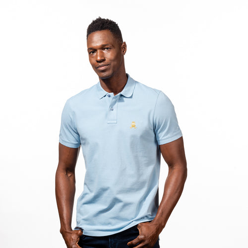 Model in light-blue polo with two-button placket, ribbed armbands, and embroidered gold frog mascot.