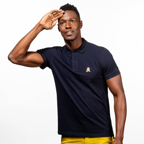 Model in navy polo with two-button placket, ribbed armbands, and embroidered gold frog mascot.