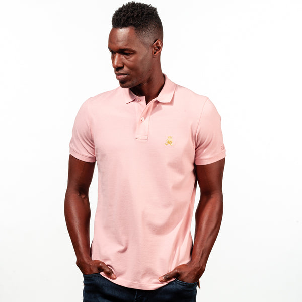Model in light-pink polo with two-button placket, ribbed armbands, and embroidered gold frog mascot.