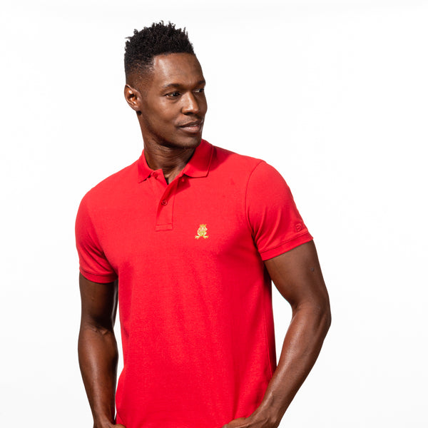 Model in red polo with two-button placket, ribbed armbands, and embroidered gold frog mascot.