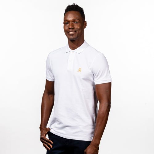 Model in white  polo with two-button placket, ribbed armbands, and embroidered gold frog mascot.