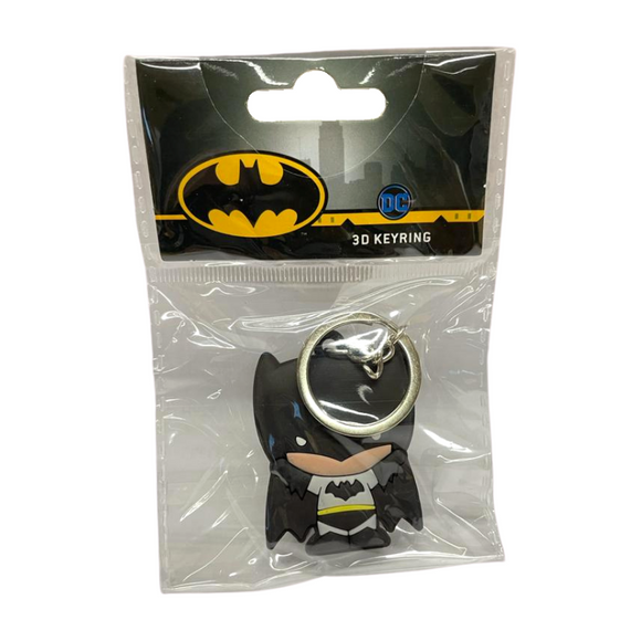 A keychain of a cartoon man with light skin in a chibi style. He is wearing a black helmet that covers the upper half of his head and has batlike ears. He is wearing a grey suit with a black bat symbol, black pants, boots and gloves, and a yellow belt, as well as a dark cape that looks like bat wings.