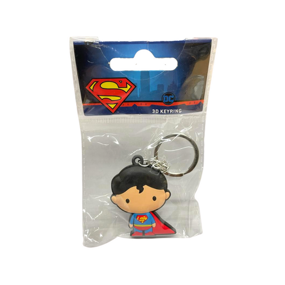 A keychain in a chibi style of a cartoon man with light skin and short dark hair that falls in a single curl over his forehead. He wears a blue costume with a red cape, red pants, red boots, and a yellow belt. A red and yellow symbol shaped like an S is on his chest.