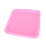 Silicone rolling tray in pink, perfectly square.  Side view.