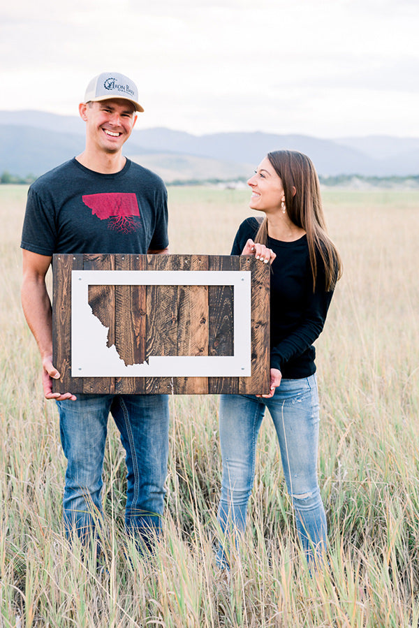 Erin and Logan holding a Montana metal sign