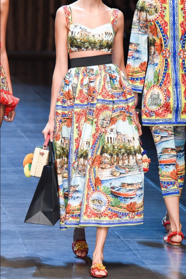 girl on runway wearing multi coloured print crop top and long skirt with bare midriff.