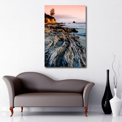 Portrait image of sunset over rock pools at sea with steep cliffs to the peripheral of the image