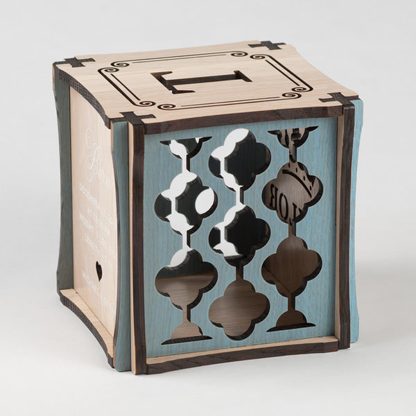 Prince Perfect CUBEMENTO™ birth cube made from Rift White Oak Hardwood with blue stained accents. Left side of cube showing laser cut graphic pattern.