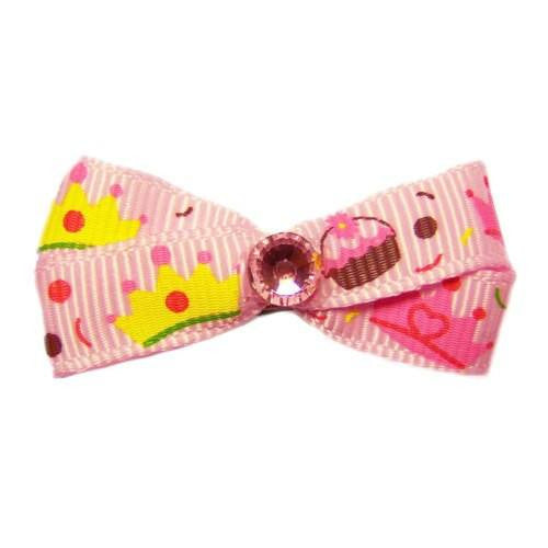 This cute pastel pink dog hair bow is printed with crowns and cupcakes.