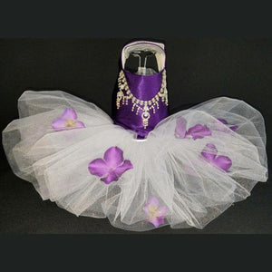 A purple satin tutu dog dress decorated with rhinestone necklace and pansy flowers.