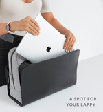 Woman placing laptop into laptop pocket of grey and black Sparro Designs work and gym tote