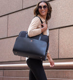 Fashionable woman holding Sparro Designs black and rose gold work tote