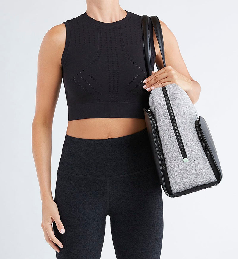 Woman in black tights and crop carrying Black Sparro Designs work and gym tote
