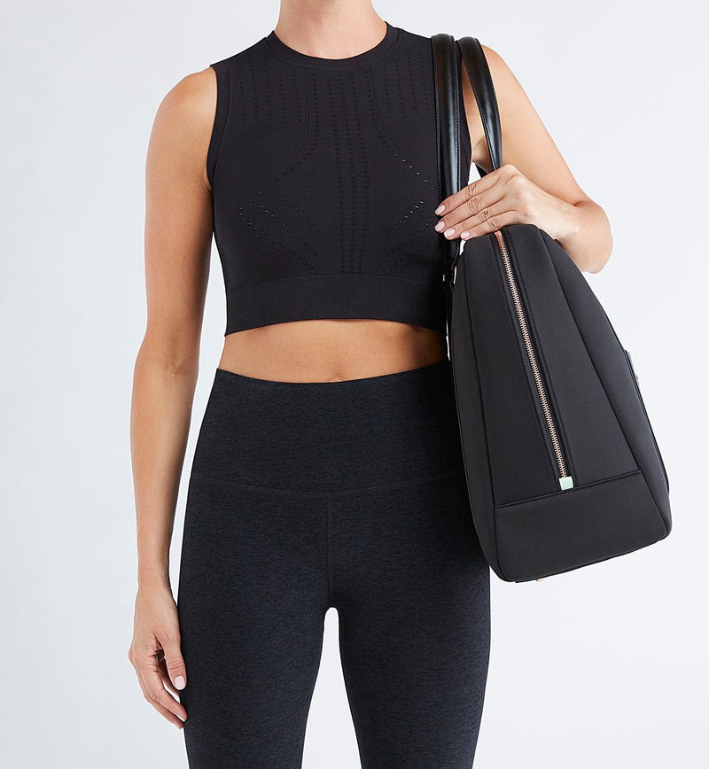 Woman in black tights and crop carrying stylish black Sparro Designs neoprene work and gym tote