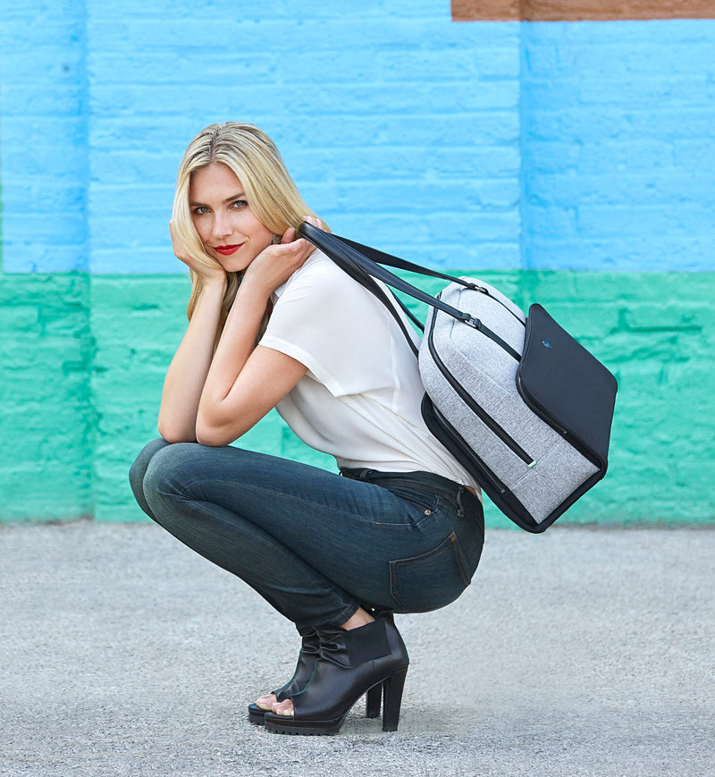 Stylish woman crouching holding fashionable grey and black neoprene work and gym bag
