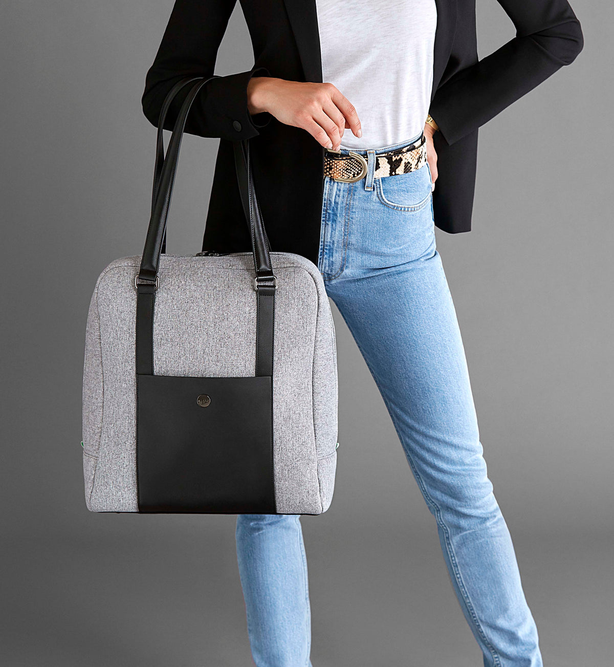 Woman holding stylish neoprene grey and black laptop and gym bag