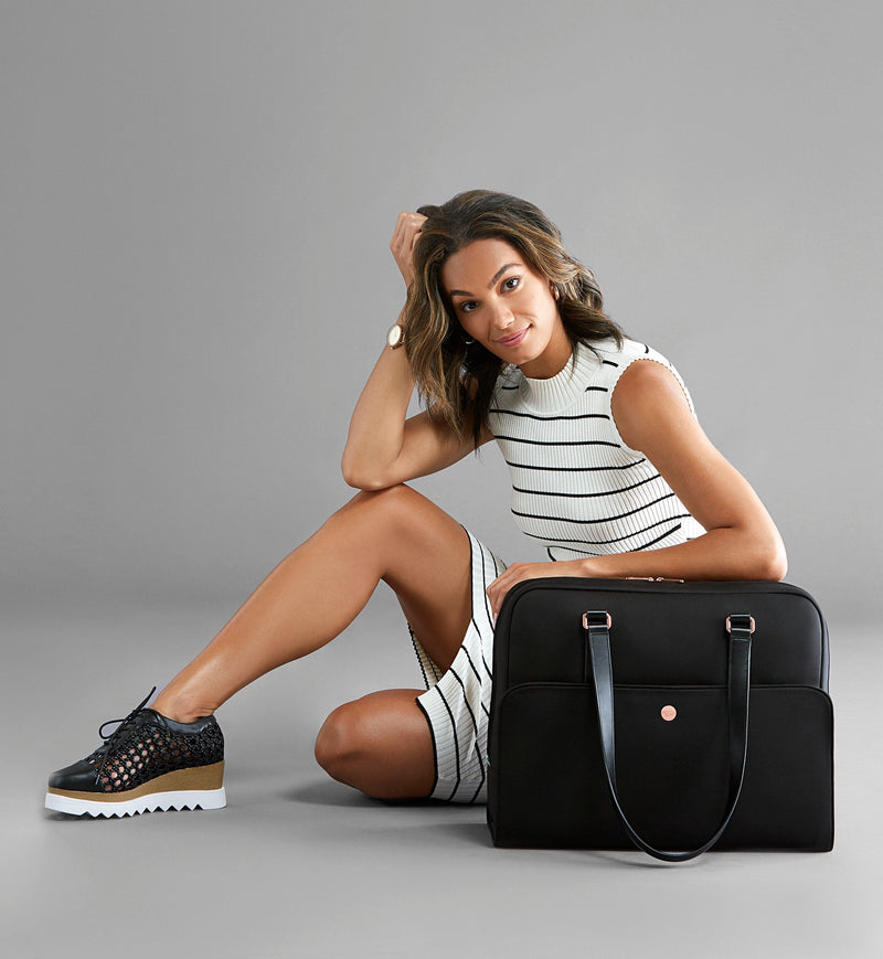 Stylish woman sitting on ground resting on luxe Black Neoprene gym and laptop tote
