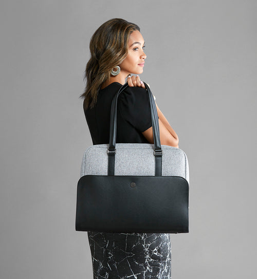 Stylish woman holding grey and black laptop and gym bag