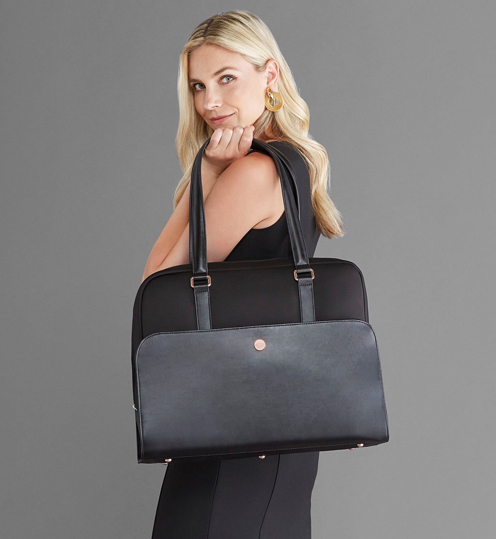 Blonde woman holding Sparro Designs black and rose gold laptop and gym bag