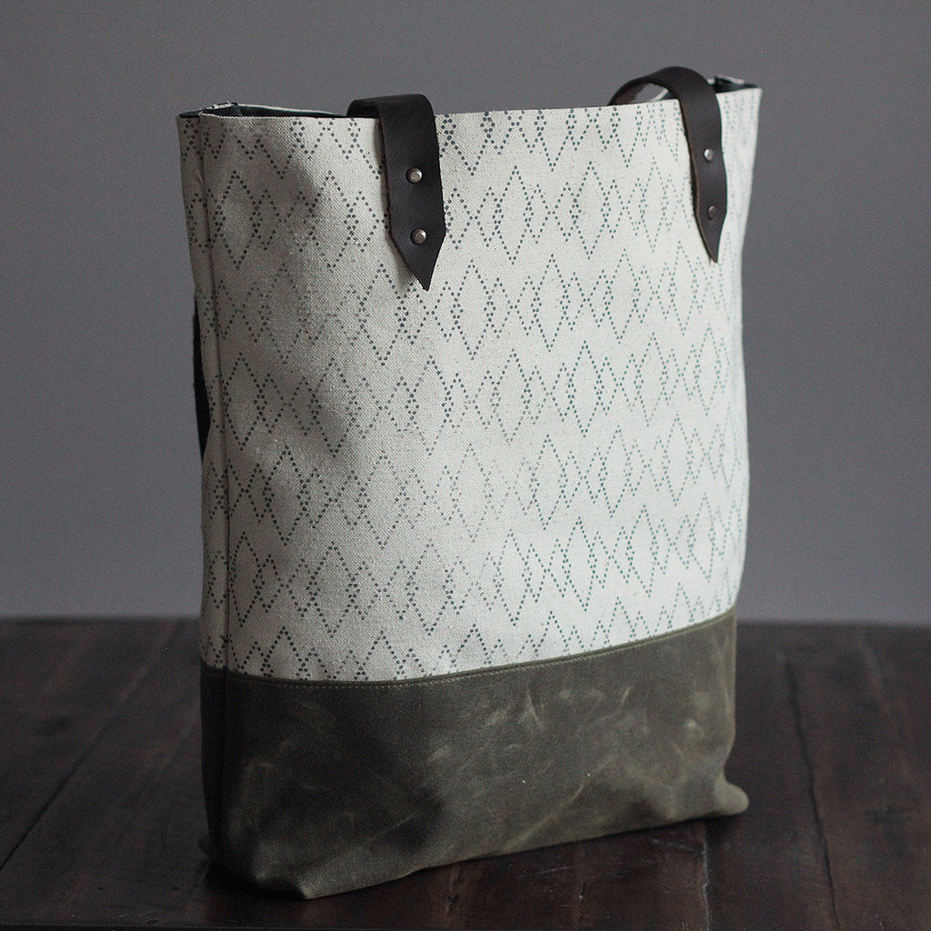 This heavyweight canvas tote is handmade in Portland, Oregon. Leather straps, screen printed fabric, waxed canvas base, interior pocket, antique brass hardware.