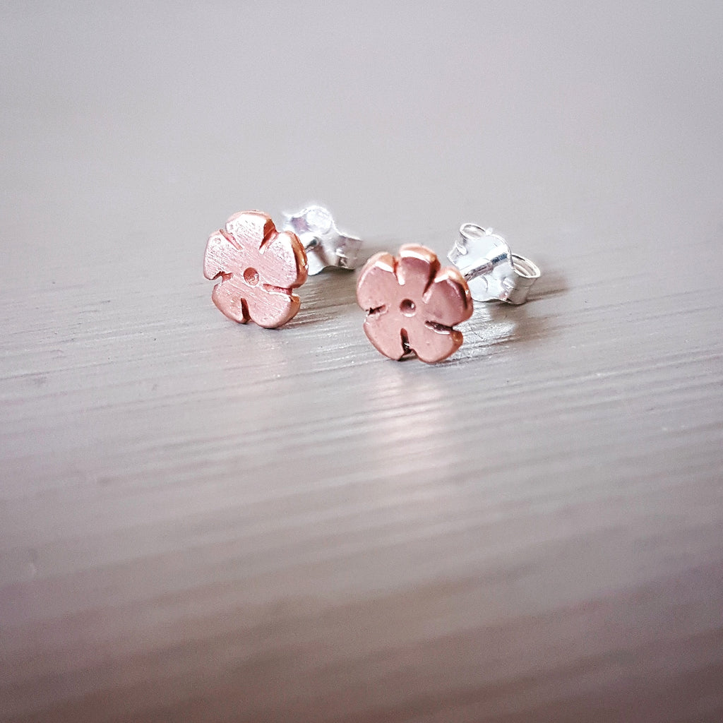 hand cut copper daisy shaped earrings made from pink copper with sterling silver posts and backs
