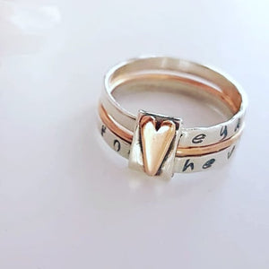 personalized silver stacking rings. 2 rings with hand stamped names and a thinner rose gold ring in between. Finished with a spinner rose gold heart.