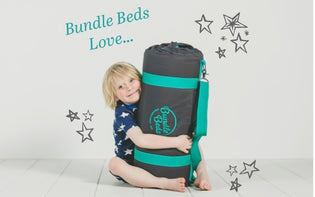 Young boy cuddles his cosy roll out sleepover Bundle Bed.