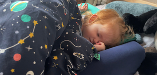 A toddler sleeps soundly on the new Tot-to-Ten travel bed by Bundle Beds