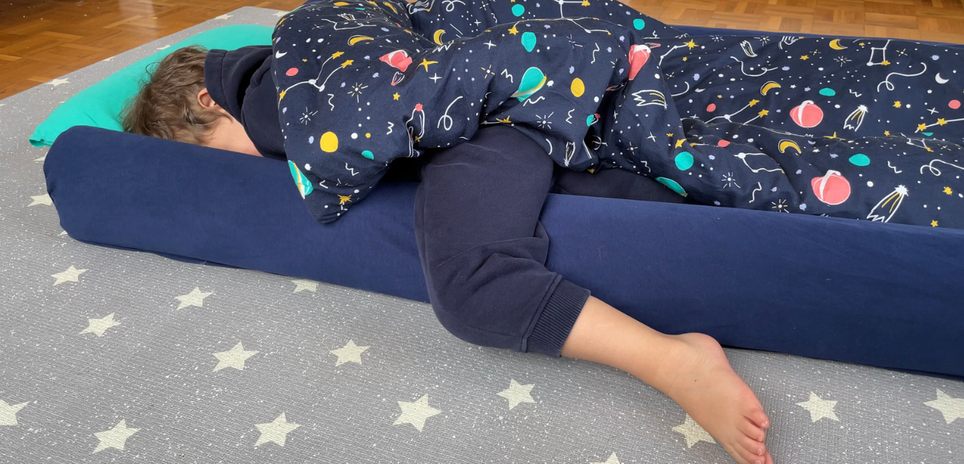 A toddler is kept safe and cosy in his travel bed by the safety bumpers