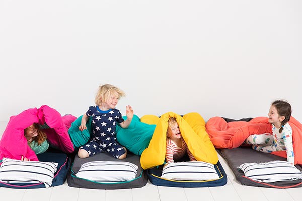 Kids laughing and having fun at a sleepover party on their roll out Bundle Beds.