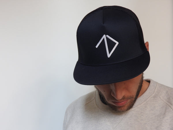 Man wearing navy trucker snapback with awesome logo
