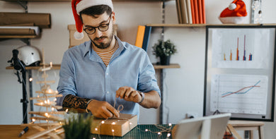 Employee wrapping Christmas gifts for colleagues for the holidays