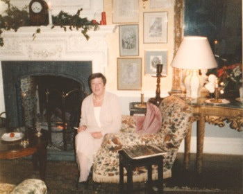 Photo of Katie's grandmother sitting on a chair in front of a fire