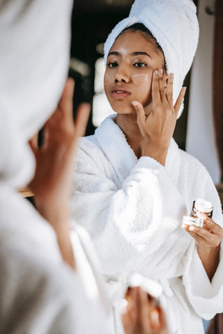 woman with towel applying cream on face