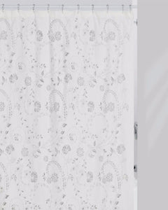White Eyelet Fabric Shower Curtain hanging on a shower curtain rod