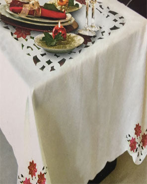 Cream Poinsettia Collection Fabric Tablecloth by Elbaz over a table