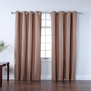 Tan Portland Room Darkening Grommet Top Panels hanging on a decorative curtain rod