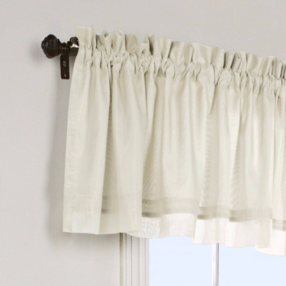 Closeup of Ivory Rhapsody Lined Tailored Valance hanging on a curtain rod
