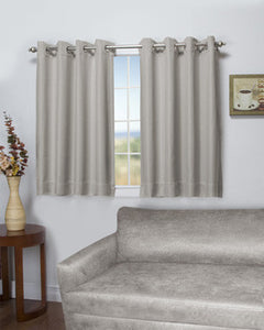 Stone Tacoma Double Blackout Shortie Grommet Top Panels hanging on a decorative curtain rod