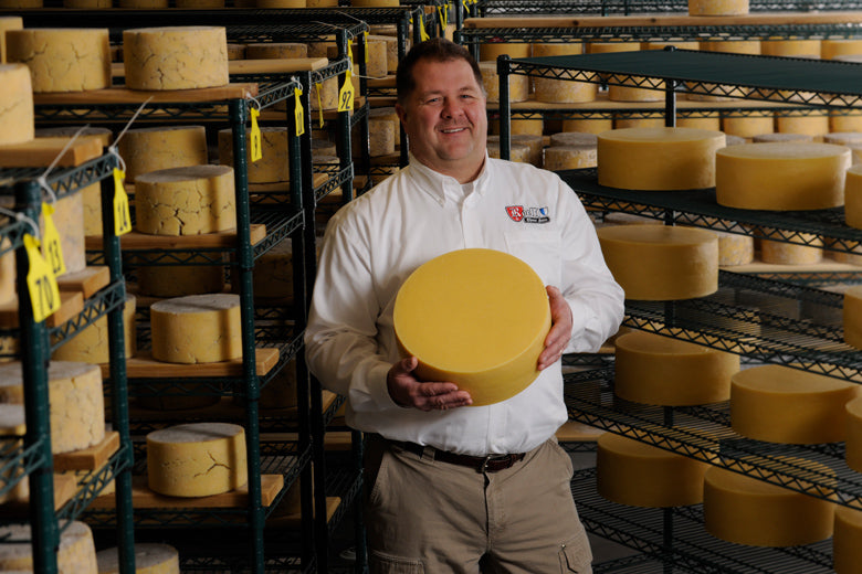 Man standing with wheel of aged cheese in cheese cellar