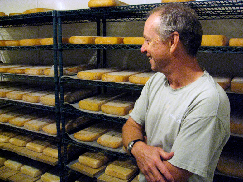 Man smiling looking at racks of cheese in a cheese cave