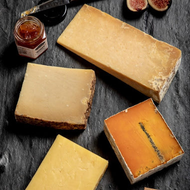 american cheddar flight - four different kinds of cheddar cheese on a cheese board with honey and figs