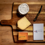 saxelby cheesemongers cheese of the month club - a selection of three cheeses on a cheese board with a cheese knife and cheese journal