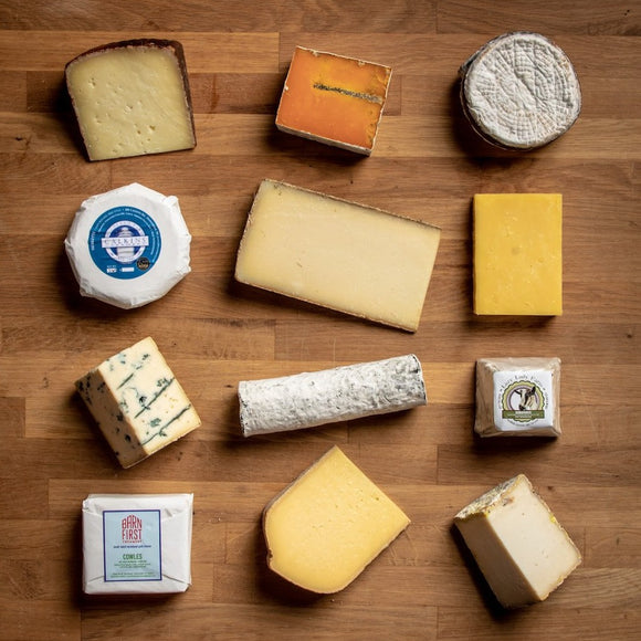 saxelby cheesemongers cheese of the month club - a selection of twelve different cheeses on a cheese board